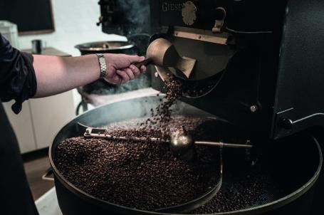 Frisk ristede kaffebønner hældes fra risteren til afkøling - Kalles Kaffe