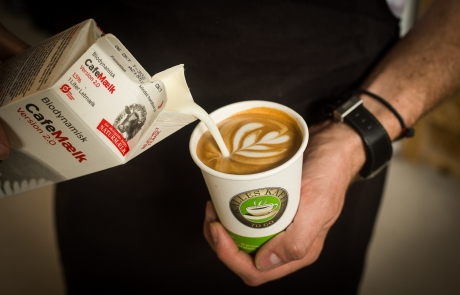 Barista pours organic milk in a caffe latte - Kalles Kaffe