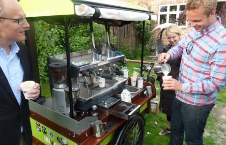Barista servere caffe latte fra kaffecykel til en havefest - Kalles Kaffe